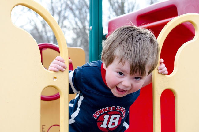 a noisy little boy yells happily from the top of a colorful slide on the playground Active Kids Boys Casual Clothing Caucasian Child Childhood Closeup Colorful Cute Day Innocence Leisure Activity Lifestyles Looking At Camera Males  Noisy Child One Person Outdoor Play Equipment Outdoors Portrait Real People Red Yell Young
