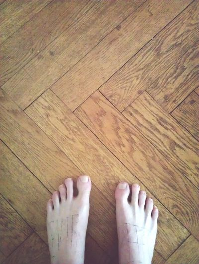 Cropped image of person standing on wooden floor