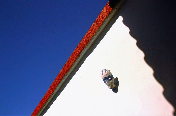 Angles And Lines Blue Clear Sky Colors And Patterns Contrasting Colors Contrasting Textures Day Dramatic Haloween Mask Hanging On The Wall Light And Shadow Lookingup Low Angle View Mask - Disguise Orange Color Outdoors Rooftile Shadows Shadows & Lights Sky Triangle Shape Urban Geometry White Washed Wall