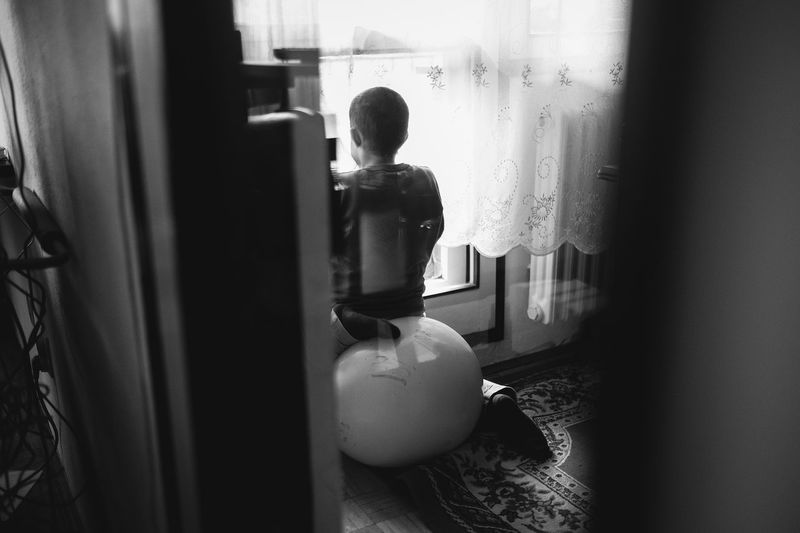 A boy with autism looking trough the window Autism Boy Child Childhood Curtain Day Full Length Indoors  Looking Through Window One Person People Real People Rear View Standing The Photojournalist - 2017 EyeEm Awards Window The Photojournalist - 2018 EyeEm Awards