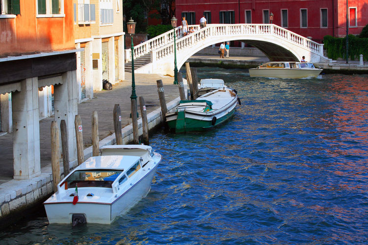 Bridge over boats on grand canal in sunny day