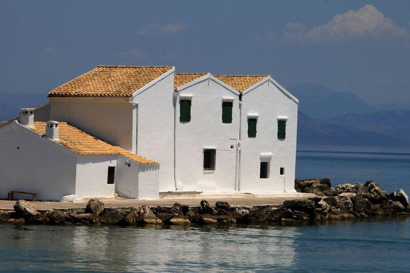 Houses by sea against sky