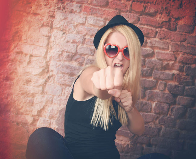 A pretty strong blond girl is punching a fist at the camera looking tough for a power, energy or confidence concept. Fight Power Adult Beautiful Woman Bravery Brick Wall Confident  Cool Attitude Front View Hipstergirl Indoors  Lifestyles Looking At Camera One Person People Personality  Portrait Punch Real People Strong Woman Style Sunglasses Tough, Young Adult Young Women