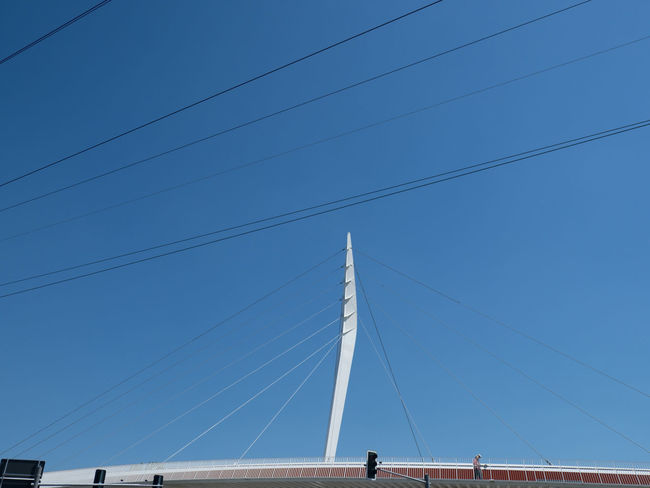 pedestrian bridge in Lahr The Architect - 2018 EyeEm Awards Architecture Blue Bridge Bridge - Man Made Structure Built Structure Cable Cable-stayed Bridge Clear Sky Connection Electricity  Engineering Low Angle View Outdoors Power Line  Power Supply Sky Technology