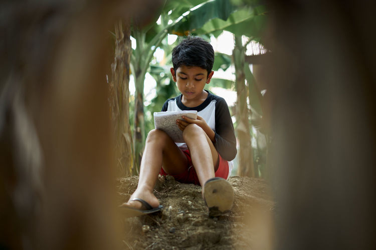 Boy writing in book while sitting outdoors