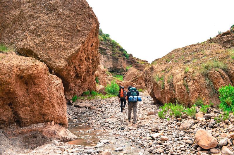 Rear view of men walking on rocks against mountain