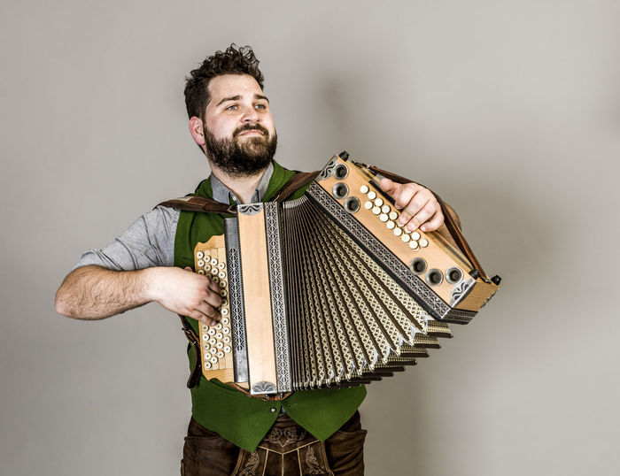 Musician Costume Leather Trousers Tradition Traditional Austria Green Pose Accordion Man Young Shorts Friendly Proud Happy Play Music Fun Joy Single One Background Copy Space Studio Entertainment Mountains Shirt STAND Hobby Leisure Cool One Person Studio Shot Young Adult Indoors  Beard Standing Young Men Front View Gray Three Quarter Length Gray Background Facial Hair Real People Arts Culture And Entertainment Looking Away Musical Instrument White Background Cut Out