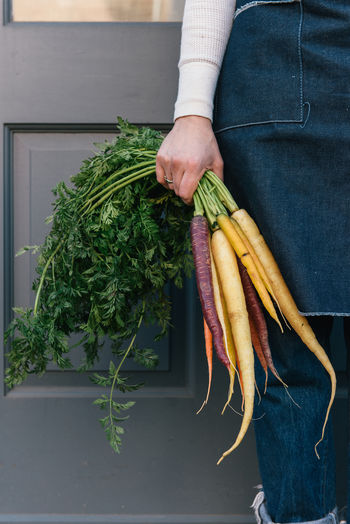 Midsection of person holding vegetables