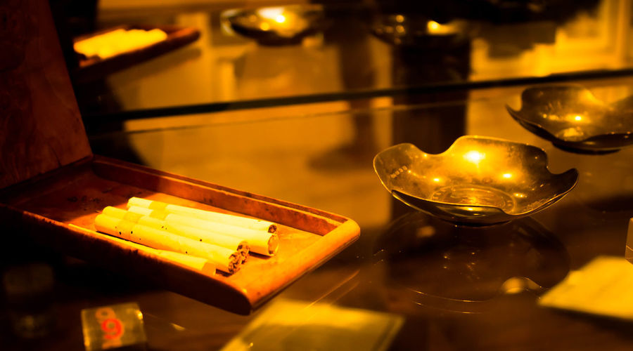 Close-up of cigarettes with ashtrays on table