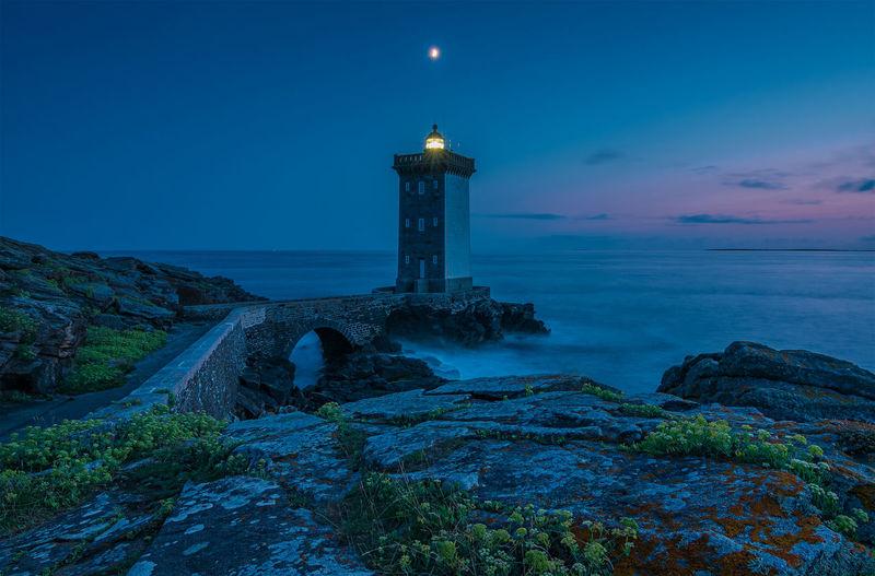 Lighthouse amidst sea and buildings against sky at dusk