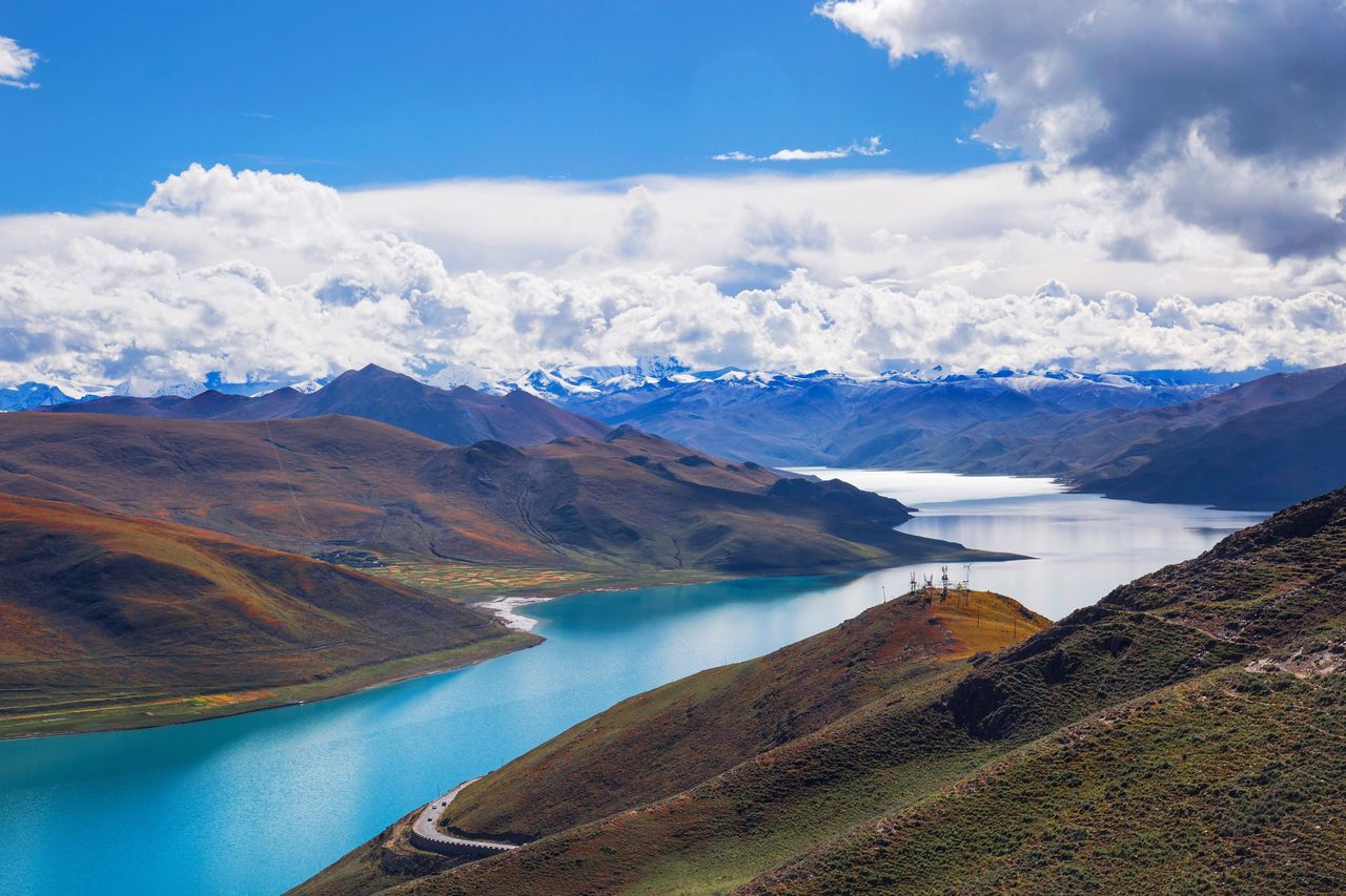 Scenic View Of Turquoise River Amidst Mountains Against Cloudy Sky