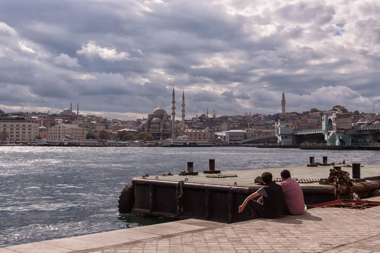 Rear View Of Friends Sitting At Harbor By Mosques In City Against Cloudy Sky
