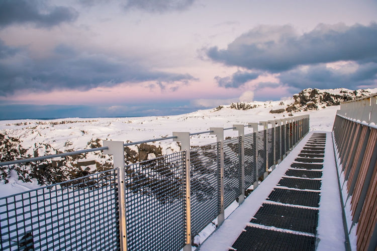 Fence by railing against sky during winter