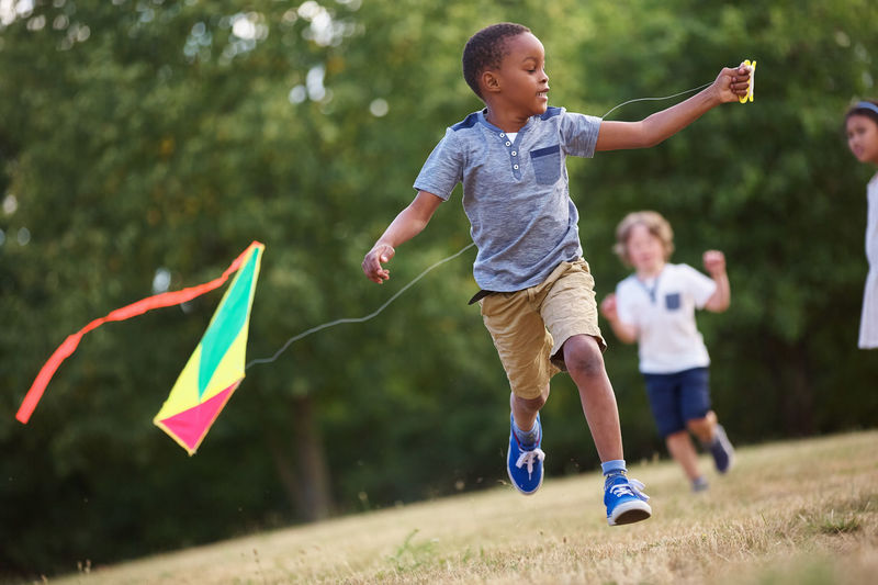 Boy running with kite at park