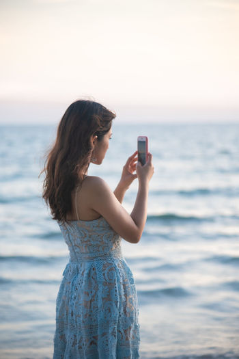 Young woman using mobile phone in sea against sky