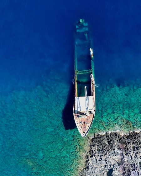 High angle view of abandoned boat in sea during sunny day