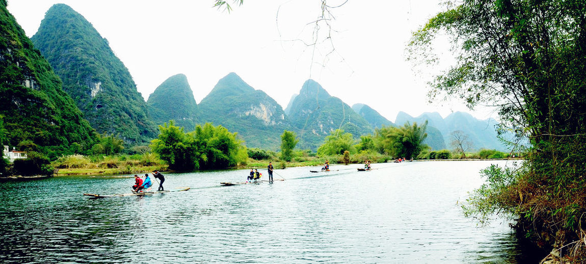 People on river by mountains against sky