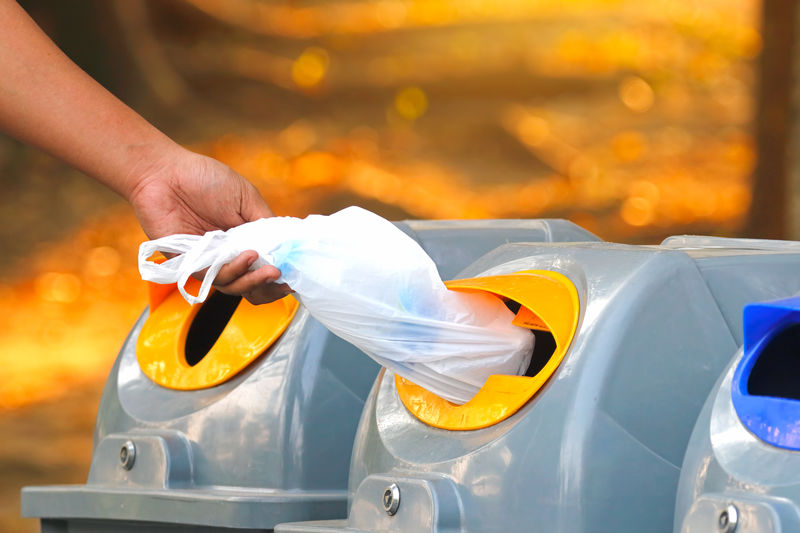 Hand throwing empty plastic bag into the recycling bin Human Hand Hand Human Body Part One Person Real People Holding Focus On Foreground Body Part Unrecognizable Person Human Finger Close-up Finger Orange Color Midsection Lifestyles Outdoors Car Day Mode Of Transportation Empty Plastic Recycling Bin