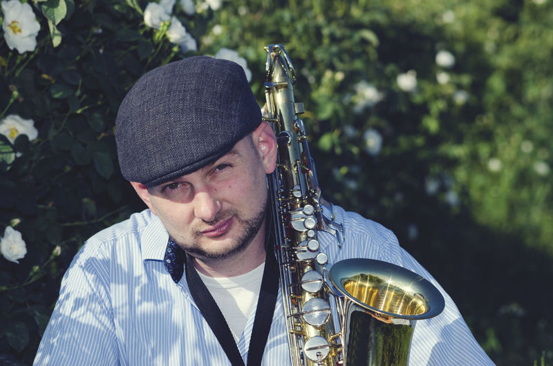 Portrait of man with saxophone against trees