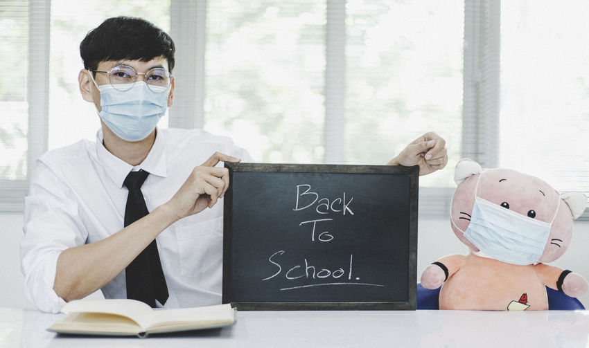 Portrait of man wearing flu mask holding slate sitting at classroom