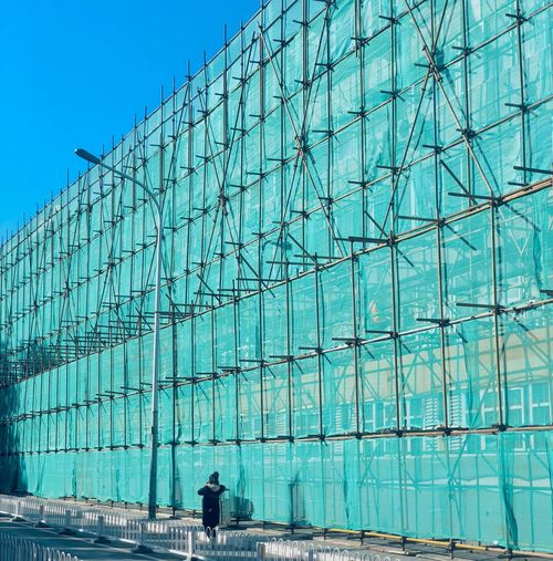 Person walking by scaffolding building in city