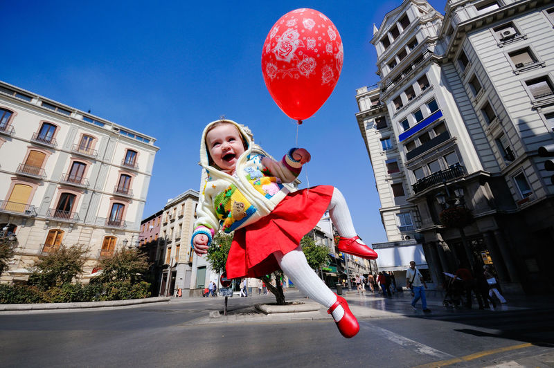 Little girl flying with a red balloon in urban background Baby Children Fun Funny Happiness Happy Happy People Winter Babygirl Child Childhood Children Photography Day Leisure Activity Lifestyles One Person Outdoors Real People Red