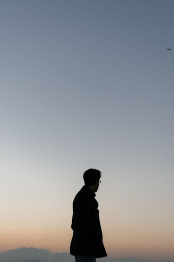 Low angle view of man against sky during sunset