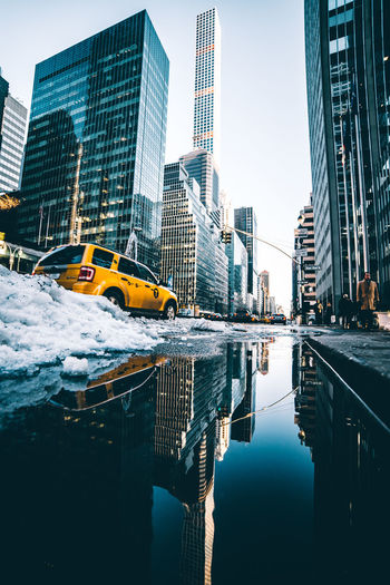 Car on snowy street by reflection against buildings