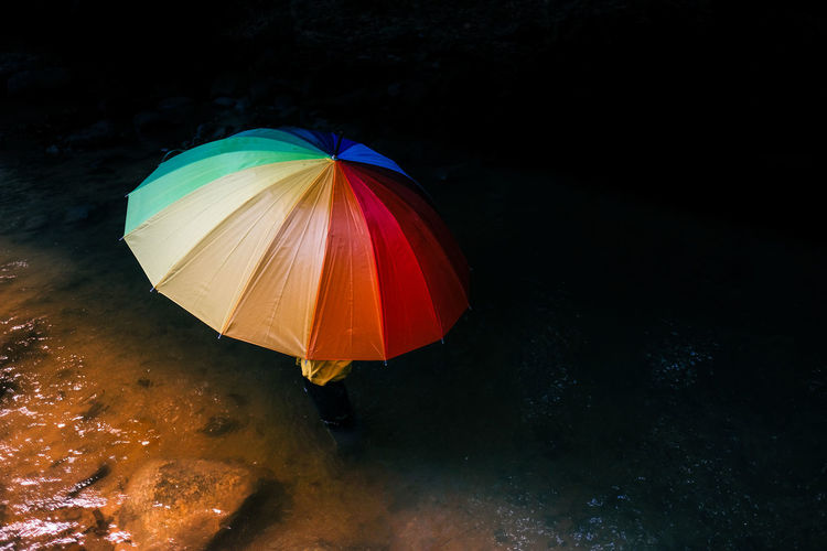 High angle view of multi colored umbrella on wet land