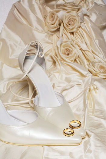 Close-up of wedding rings on high heels and dress