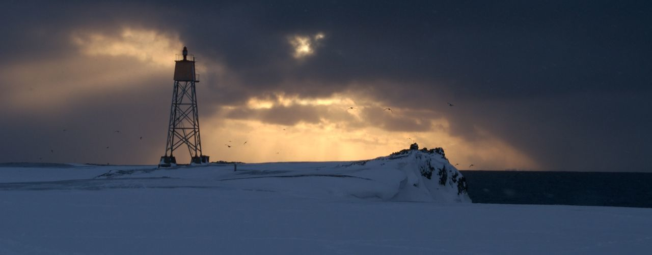 Lighthouse On Snowcapped Landscape By Sea Against Sky At Spitsbergen