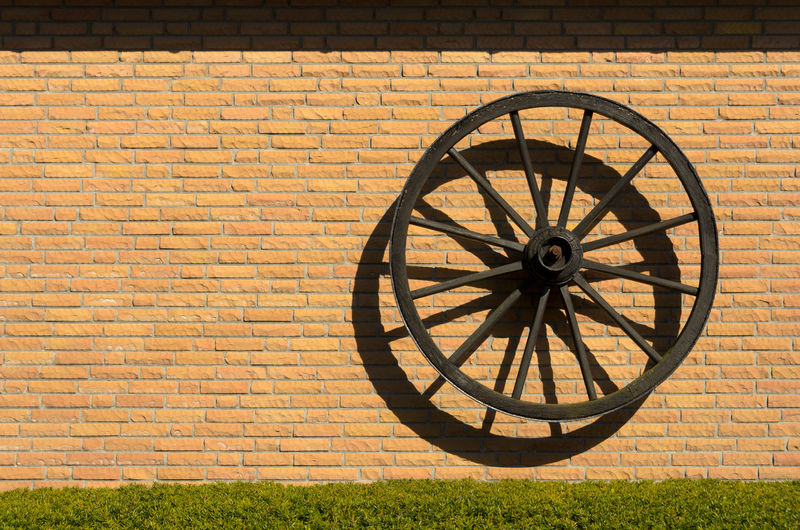 Shadow of wheel on brick wall