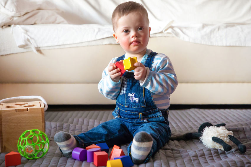 Babyboy Baby Casual Clothing Child Childhood Cute Down Syndrome Flooring Front View Full Length Furniture Holding Indoors  Innocence Lifestyles Mental Health  One Person Relaxation Sitting Sofa Toy Toy Block Young