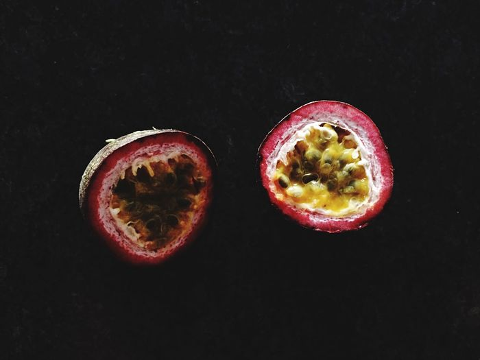 Sliced Passion Fruit Against Black Background
