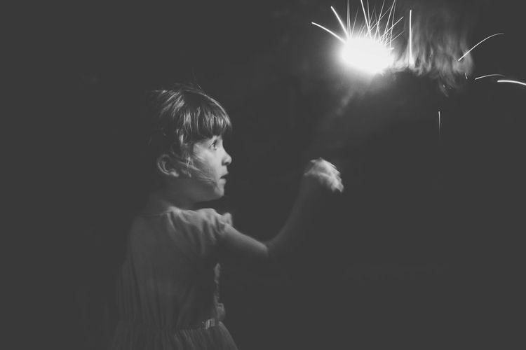 Close-up of boy standing against illuminated lights