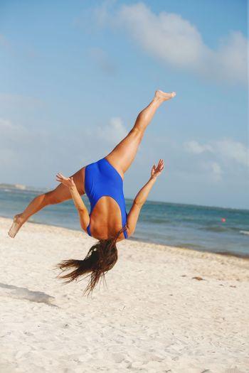 Full length of woman jumping at beach at beach