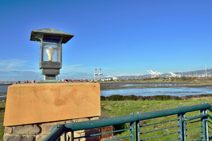 Observation Tower 4 Middle Harbor Scenic View Port Of Oakland, Ca Brick Column Of Tower Lamp On Top Of Tower Column Gantry Cranes Eastbay Hills Estuary Inner Harbor Low Tide Port Containers Lamp Posts Blue Sky Clouds Mudflats Waterfowl In Mudflats Schrubs Grass Architecture Architectural Feature Landscape Landscape_photography Landscape_Collection Nature