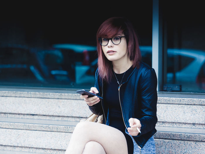 Portrait of woman using mobile phone and flicking cigarette while sitting on bench