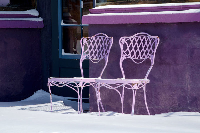 two purple metal chairs sit outside a purple building in the winter Weather Building Exterior Chair Close-up Cold Temperature Day Fancy Pattern Metal Chairs Outdoors Outdoors Photograpghy  Purple Chairs Seasonal Snow Winter