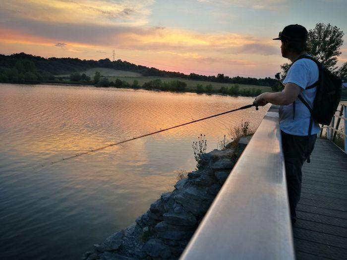 Side View Of Man Fishing At Lake During Sunset