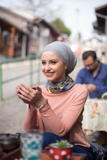 Smiling young woman wearing headscarf while sitting at table