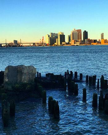 By the water Architecture Beauty In Nature Built Structure City Cityscape Clear Sky Day East River, NYC Nature No People Outdoors Rock Sea Sky Skyscraper Sunset Travel Destinations Urban Skyline Water