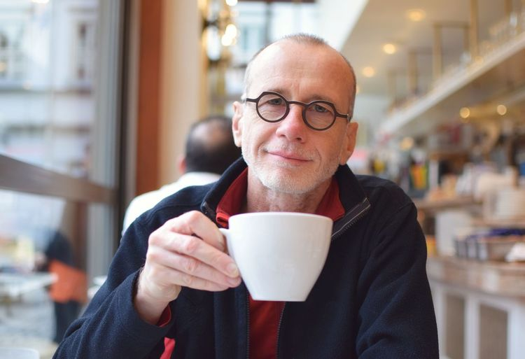 Portrait of mature man drinking coffee while sitting by window in cafe