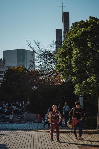 People on sidewalk against buildings in city