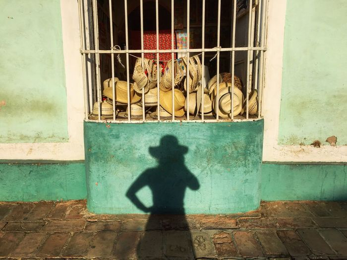 Perusing the hat collection at sundown in Trinudad, Cuba. Silhouette That's Me Tranquil Scene Hat Shadows & Lights Shadow Cuba Window Window Shopping Green Color IPhoneography Travel Photography The Adventure Handbook The Week On EyeEm The Week On EyeEm