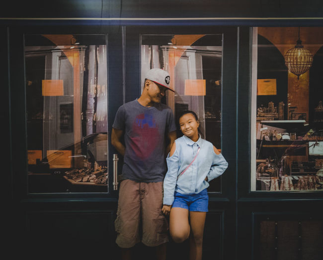Smiling father and daughter standing against store
