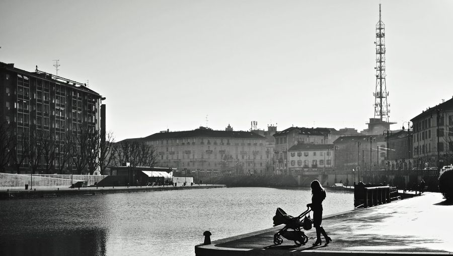 Woman With Baby Carriage By River In City