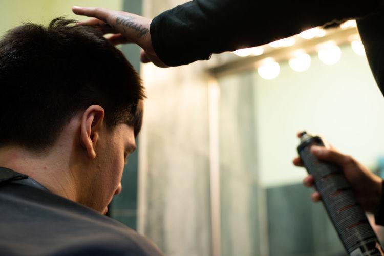 Barber adjusting hair of man at salon