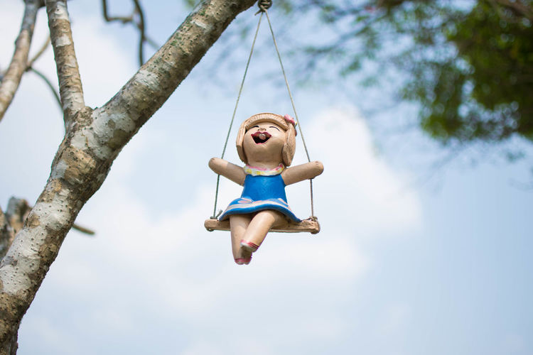 Low angle view of woman sitting on swing