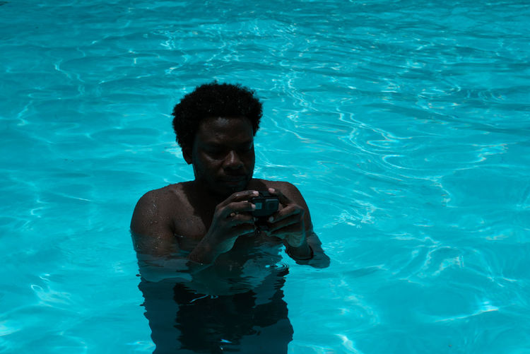 Standing... TheWeekOnEyeEM Day Front View Holding Leisure Activity Lifestyles Men Nature One Person Outdoors Pool Real People Shirtless Standing Swimming Pool Technology Waist Up Water Wireless Technology Young Adult Young Men